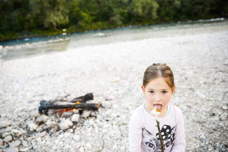 scouts: Little girl eating roasted marshmallow by a self-made campfire on camping trip by the mountain river. Active natural lifestyle, childhood concept.
