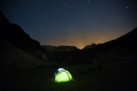 bivouac: Lone, lit pop-up tent standing on a mountain pasture under the starry sky, night landscape with bright sun flare in the background. Outdoor lifestyle and sleeping under stars concept and background.