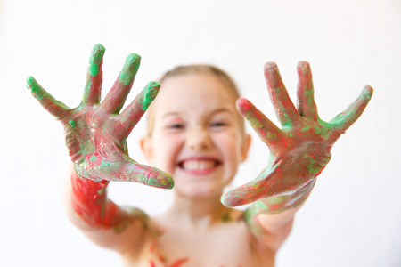 sharpness: Little girl showing her hands, covered in finger paint after painting a picture and her body with it. Playfulness, creativity, permissive parenting, fun childhood concept, selective sharpness. Stock Photo