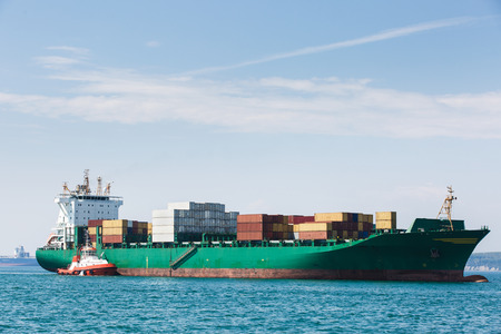 escorted: Big container ship, loaded with various colorful containers, waiting to be assisted and escorted to the port by a towboat. Global transportation, global business, consumerism concept and background. Stock Photo