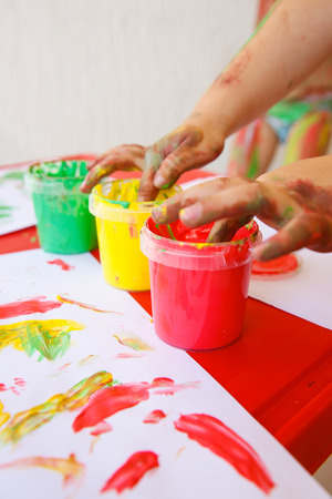 Child dipping fingers in washable, non-toxic finger paints, painting a drawing. Sensory play, innovative learning and creativity, fun childhood concept.