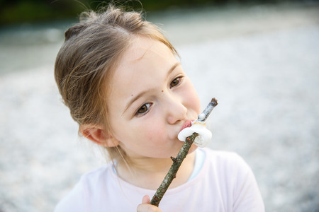 scouts: Little girl eating roasted marshmallow on camping trip by the mountain river. Active natural lifestyle, fun childhood concept.