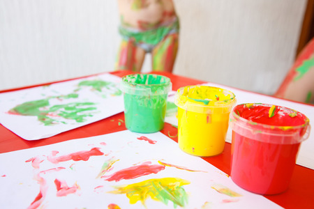 Finger paints in bright colors, used for finger drawings and sensory play, with drawings and body painted girl in the background. Innovative approach to learning, fun childhood concept. Stock Photo