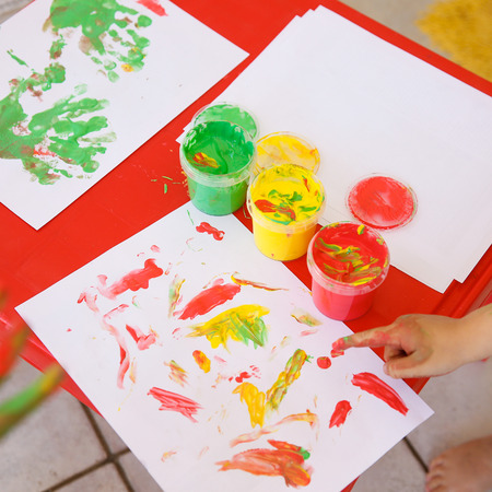 Child painting a drawing with finger paints, used for finger drawing and sensory play. Fun childhood, sensory and experience-based learning concept.