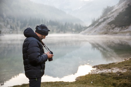 winter photos: Photographer on assignment, holding a camera, checking photos after photographing in the morning by a mountain lake with winter mist covered surface.