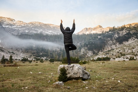 spiritual: Man practicing yoga, greeting the sun, performing a tree pose (vrksasana) in morning in beautiful mountain landscape in late winter. Spirituality, meditation, wellness and healthy lifestyle concept. Stock Photo