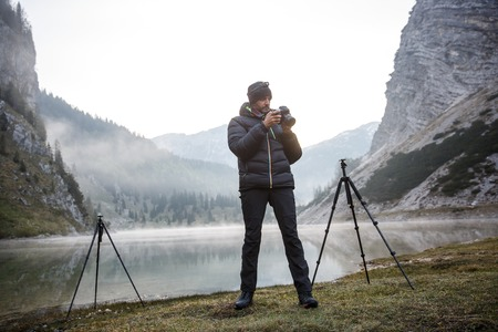 photo shooting: Photographer on assignment, holding a camera, checking photos after photographing in the morning by a mountain lake with winter mist covered surface.