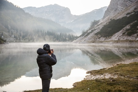 photographer: Photographer on assignment, holding a camera, taking photos of beautiful mountain landscape in the morning by a mountain lake with winter mist covered surface.