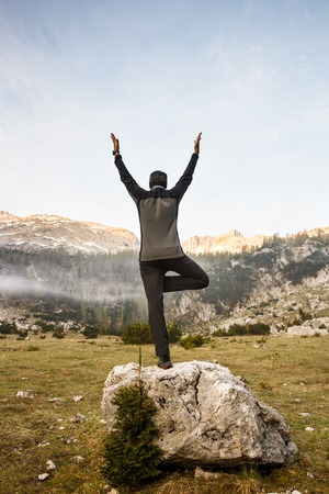 yoga to cure health: Man practicing yoga, saluting the sun, performing a tree pose (vrksasana) in morning in beautiful mountain landscape in late winter. Spirituality, meditation, wellness and healthy lifestyle concept.