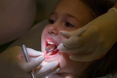 preventive: Little girl at pediatric dentists office, being examined by her dentist. Early prevention, oral hygiene and milk teeth care concept.