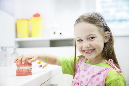niño modelo: Niña que sostiene un modelo artificial de la mandíbula humana con los apoyos dentales en la oficina de ortodoncia, sonriendo. Odontopediatría, odontología estética, educación temprana y el concepto de la prevención.