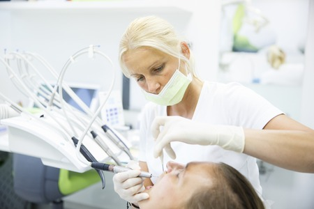 periodontal disease: Patient and her dentist, doing a comprehensive examination on regular checkup at dental office, checking for caries and periodontal disease. Oral hygiene, dental care, preventive procedures concept.