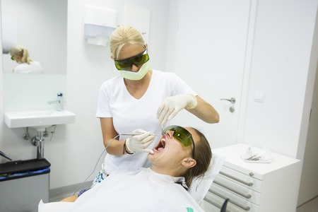 preventing: Dental hygienist using a modern diode dental laser for periodontal care, wearing protective glasses, preventing eyesight damage. Periodontitis, dental hygiene, preventive procedures concept.