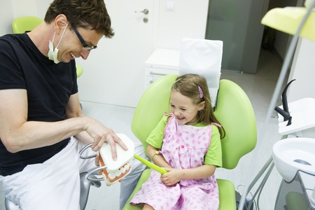 toothbrushing: Smiling little girl having fun with her pediatric dentist, brushing a dental model, being educated about proper tooth-brushing. Early prevention, oral hygiene demonstration concept.
