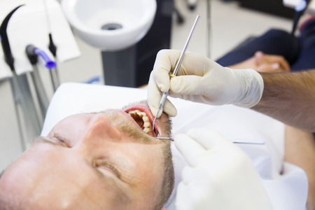 periodontal disease: Patient in dental office, having a comprehensive examination done on regular checkup, checking for caries and periodontal disease. Oral hygiene, dental care, preventive procedures concept.