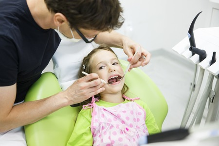 dentist: Child patient in paediatric dentists office on her regular checkup for tooth decay, caries and gum disease. Early prevention, oral hygiene and milk teeth care concept.