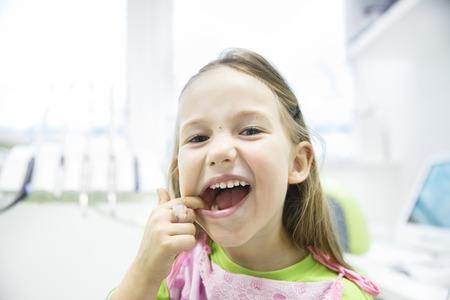 Niña Relajado mostrando sus dientes de leche sanos en el consultorio dental, sonriendo y esperando para un chequeo. La prevención temprana, paedodontics y ningún concepto el miedo.