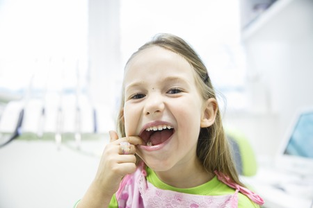 no fear: Relaxed little girl showing her healthy milk teeth at dental office, smiling and waiting for a checkup. Early prevention, paedodontics and no fear concept.