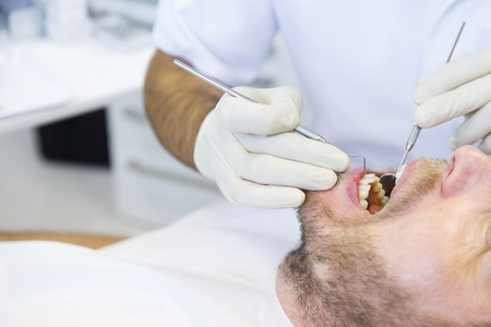 Patient in dental office, having a comprehensive examination done on regular checkup, checking for caries and periodontal disease. Oral hygiene, dental care, preventive procedures concept. Banco de Imagens - 43619649