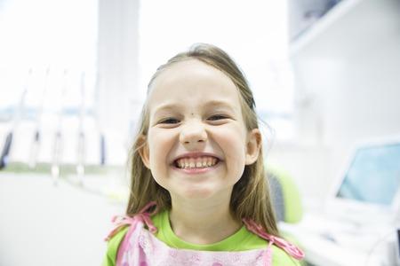 dientes sanos: Niña Relajado mostrando sus dientes de leche sanos en el consultorio dental, sonriendo y esperando para un chequeo. La prevención temprana, paedodontics y ningún concepto el miedo.