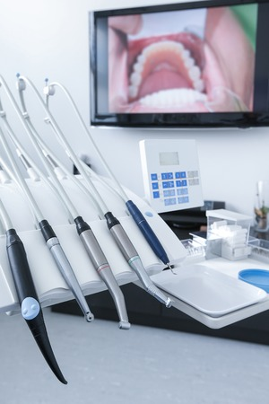drills: Dental office - specialist tools, drills, handpieces and laser with live picture of teeth in the background. Dental care, dental hygiene, checkup and therapy concept. Stock Photo
