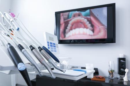 caries dental: Consultorio odontológico - herramientas especializadas, taladros, piezas de mano y láser con imagen en vivo de los dientes en el fondo. Cuidado dental, higiene dental, chequeo y el concepto de la terapia. Foto de archivo