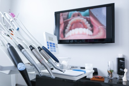 exam room: Dental office - specialist tools, drills, handpieces and laser with live picture of teeth in the background. Dental care, dental hygiene, checkup and therapy concept. Stock Photo