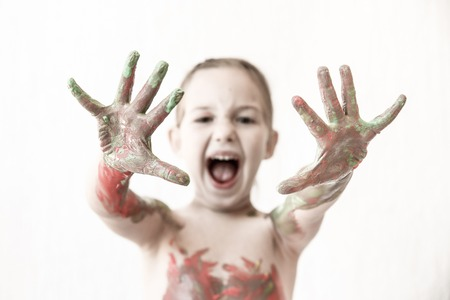 sharpness: Little girl showing her hands, covered in finger paint after painting her body with it. Playfulness, creativity, permissive parenting, fun childhood concept, selective sharpness, desaturated.