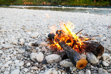 Self-made campfire by the mountain river, lit for cooking, roasting and water purification. Safety and survival, fun family activity concept.