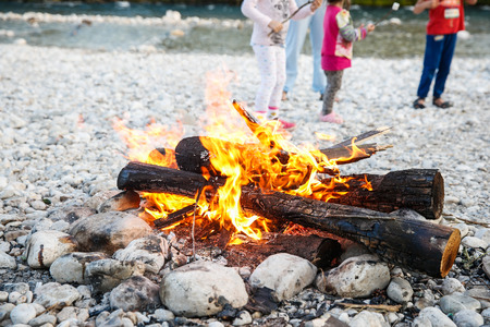 adventure: Family enjoying time by the river and self-made campfire during adventurous camping trip, spending quality tome together.  Active natural lifestyle, family time concept. Stock Photo