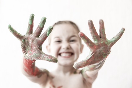 finger paint: Little girl showing her hands, covered in finger paint after painting her body with it. Tactile play, innovative learning, permissive upbringing, fun childhood concept, blur, desaturated.
