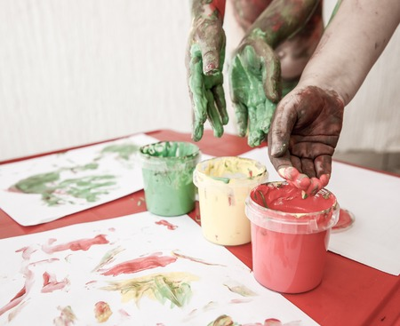 washable: Children dipping fingers in washable, non-toxic finger paints, painting a drawing. Sensory play, permissive parenting, fun childhood concept, desaturated. Stock Photo
