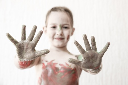 body paint: Little girl showing her hands, covered in finger paint after painting her body with it. Tactile play, innovative learning, permissive upbringing, fun childhood concept, blur, desaturated.