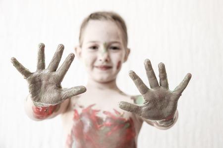body paint: Ni�a que muestra sus manos, cubiertas de pintura de dedos despu�s de pintar su cuerpo con �l. Juego t�ctil, aprendizaje innovador, la crianza permisiva, diversi�n concepto de infancia, falta de definici�n, desaturado.