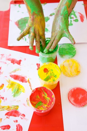 washable: Child dipping fingers in washable, non-toxic finger paints, painting a drawing. Sensory play, innovative approach to learning, fun childhood, back to school concept. Stock Photo