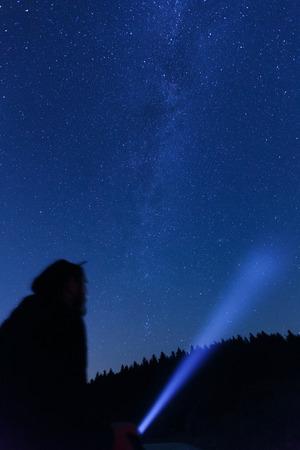 astronomie: Silhouette eines Mannes mit einer Taschenlampe, die Beobachtung schönen, breiten blauen Nachthimmel mit Sternen und sichtbare Milchstraße. Astronomie, Orientierung, klaren Himmel Konzept und Hintergrund.