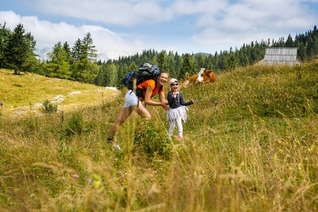 quality time: Mother tickling her daughter on mountain hike in the Alps, having fun, spending quality time together, with huts and cows in background. Active parenting, fun childhood and family bonding concept.