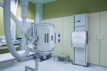 X-ray room in a hospital ER operating room with a classic ceiling-mounted x-ray system. Modern medical equipment, interventional medicine and healthcare concept.