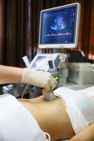 Doctor in a hospital diagnostic room doing an ultrasound of a patient abdomen with convex probe. Modern medical equipment, preventional medicine and healthcare concept.