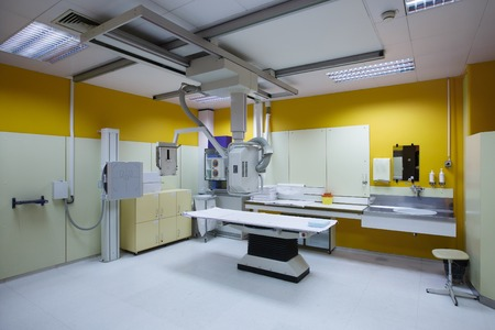 radiographic: X-ray room in a hospital ER operating room with a classic ceiling-mounted x-ray system. Modern medical equipment, interventional medicine and healthcare concept.