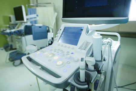 internal: Medical ultrasound machine with linear probes in a hospital diagnostic room. Modern medical equipment, preventional medicine and healthcare concept.