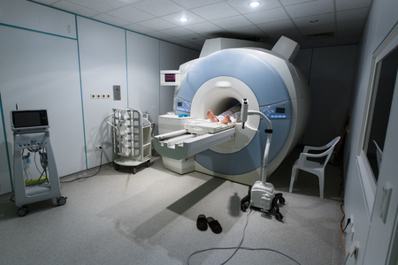 Patient being scanned and diagnosed on a MRI magnetic resonance imaging scanner in a hospital. Modern medical equipment, medicine and health care concept.