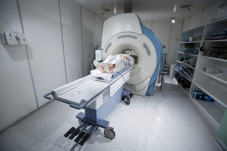 MRI magnetic resonance imaging scanner in a hospital, with patient being scanned and diagnosed. Modern medical equipment, medicine and health care concept. Standard-Bild