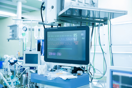 heart rate monitor: Functional vital functions (vital signs) monitor in an operating room with machines in the background, during real surgery on a patient. Life sustainment, monitoring and anesthesia concept.