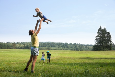 active woman: Mother playing with children, throwing a toddler in air, laughing and playing, and her older son and daughter jumping and running on a meadow. Active lifestyle, family time, modern parenting concept.