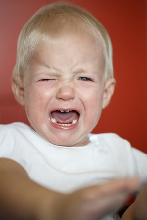 maldestro: Piccolo, pianto bambino in dolore dopo la caduta verso il basso, imparare a camminare. Infanzia, fase goffo, concetto di genitorialità difficile.