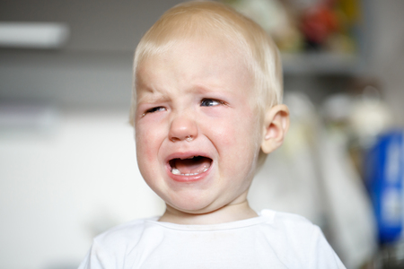 developmental: Small and sick crying toddler in pain. Childhood illnesses, developmental phases, hard parenthood concept.