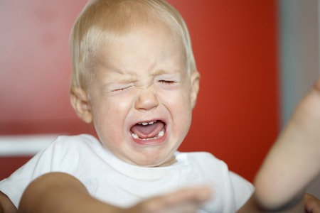 aggressive: Small, crying and kicking toddler having a temper tantrum at home, defying parents. Childhood, developmental phase, hard parenthood concept. Stock Photo