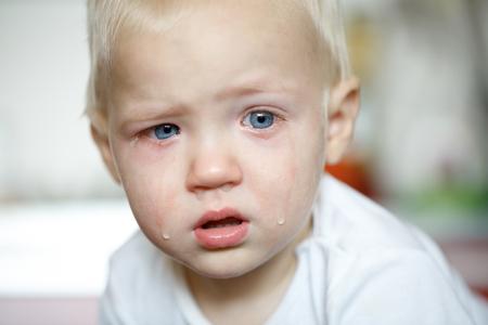 Kleine, huilende peuter pijn met ontstoken ogen. Kinderziekten, onhandig fase, hard ouderschap concept.