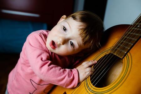 instrumentos musicales: Pequeño niño escuchando y cantando a los sonidos, que sale de una guitarra. educación musical, experiencias táctiles y el concepto de aprendizaje.
